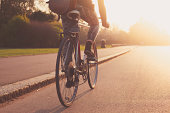 istock Young woman cycling in the park at sunset 493958393