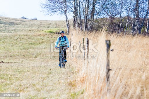 Young Woman Cycling Near the Pasture