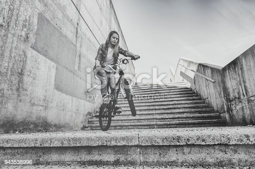 812812808istockphoto Young woman cycling with flatland bmx 943538996