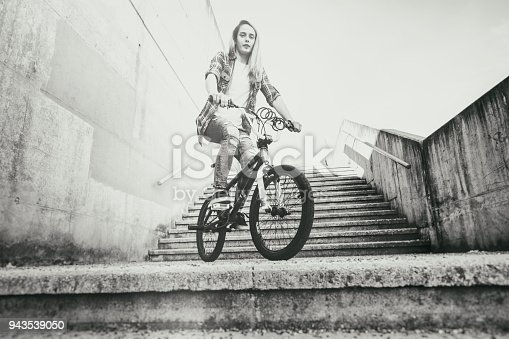 812812808istockphoto Young woman cycling with flatland bmx 943539050
