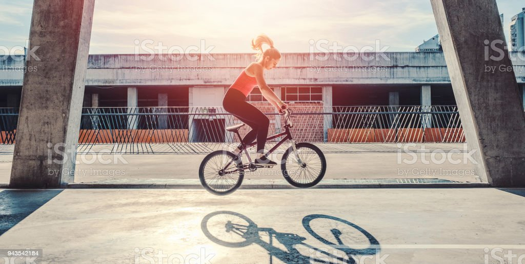 Young woman cycling with flatland bmx stock photo