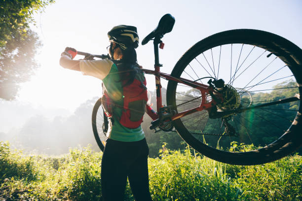 Young woman cyclist carrying mountain bike on summer forest trail stock photo