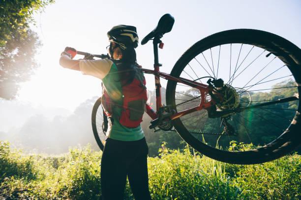 young woman cyclist carrying mountain bike on summer forest trail - занятия на открытом воздухе стоковые фото и изображения