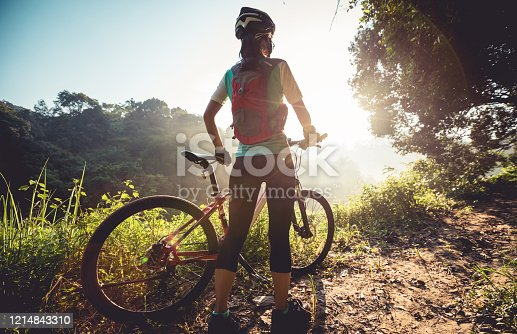 Young woman cyclist  enjoy the beautiful sunrise on summer forest trail