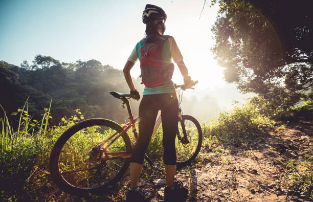 Young woman cyclist  enjoy the beautiful sunrise on summer forest trail stock photo