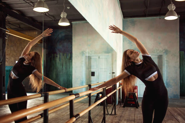 joven bailarina calentando cerca del ballet Barre - foto de stock