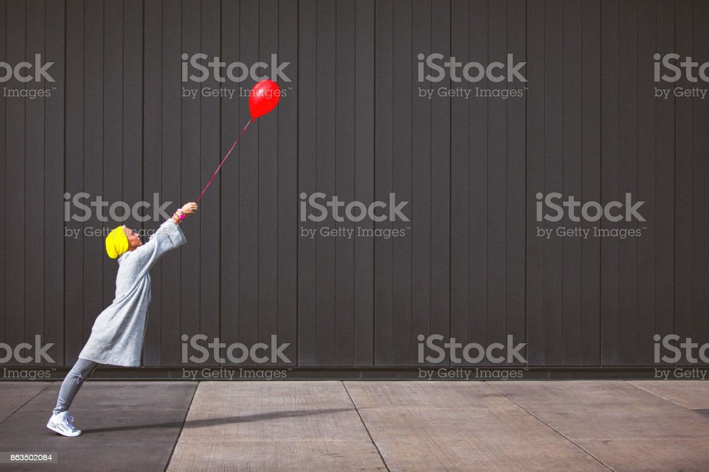 Jovem mulher dançando e segurando o balão vermelho contra a parede cinza - Foto de stock de 20 Anos royalty-free