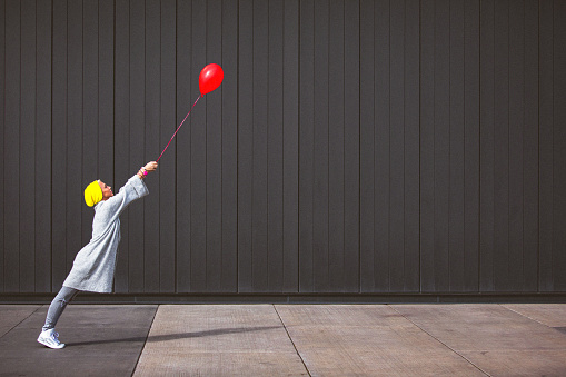 istock Young woman dancing and holding red balloon against the grey wall 863502084