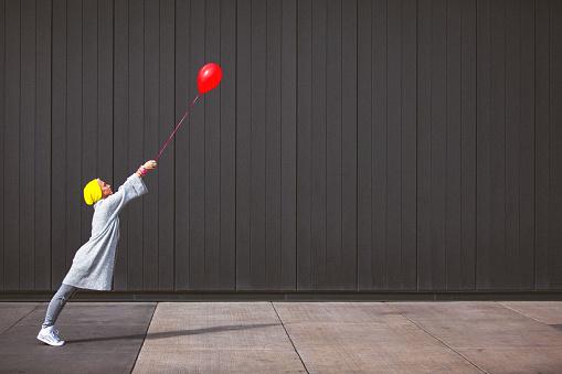 Foto de Jovem Mulher Dançando E Segurando O Balão Vermelho Contra A Parede Cinza e mais fotos de stock de 20 Anos