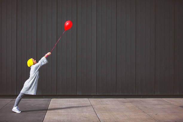 Young woman dancing and holding red balloon against the grey wall stock photo