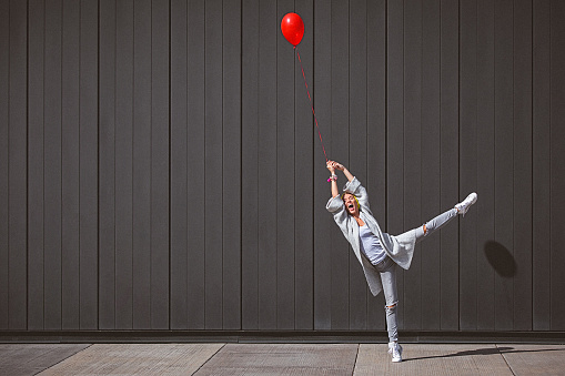 istock Young woman dancing and holding red balloon against the grey wall 863505326