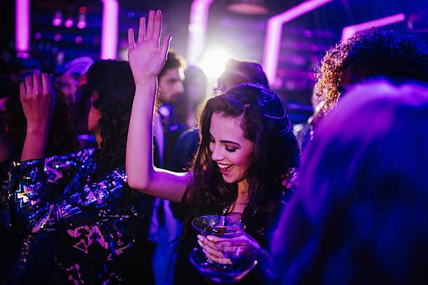 Jeune femme danse dans un club, avec un cocktail - Photo