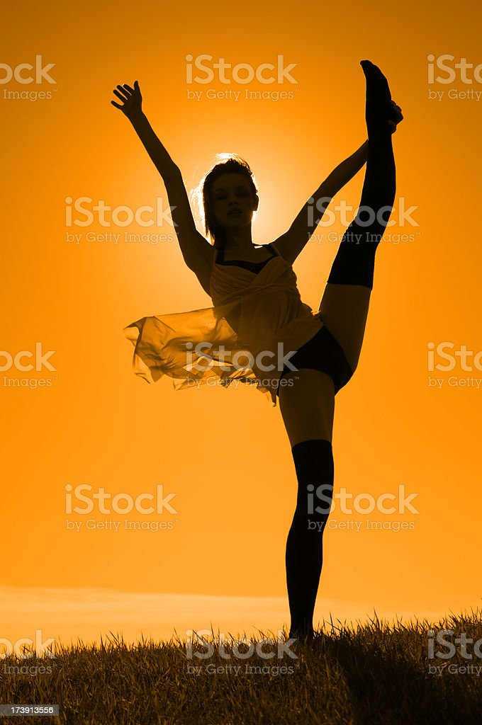 Young Woman Dancing on Hill in Summer Breeze, Golden Sky royalty-free stock photo