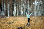 A cheerful Russian girl hiker is walking in the forest. She is standing on the stump and dancing with hands up. The girl smiling and looking at the camera. Shooting at overcast autumn day