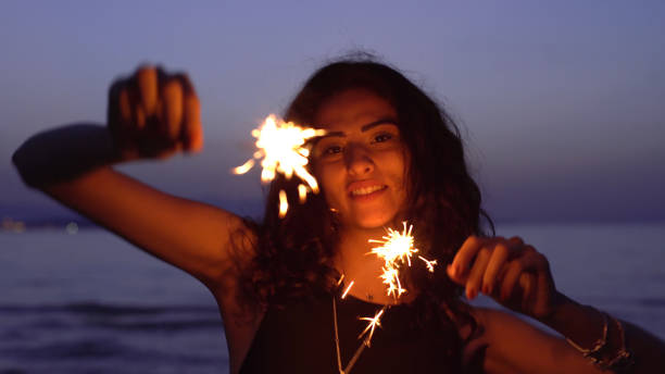 Young woman dancing with sparklers on the beach stock photo