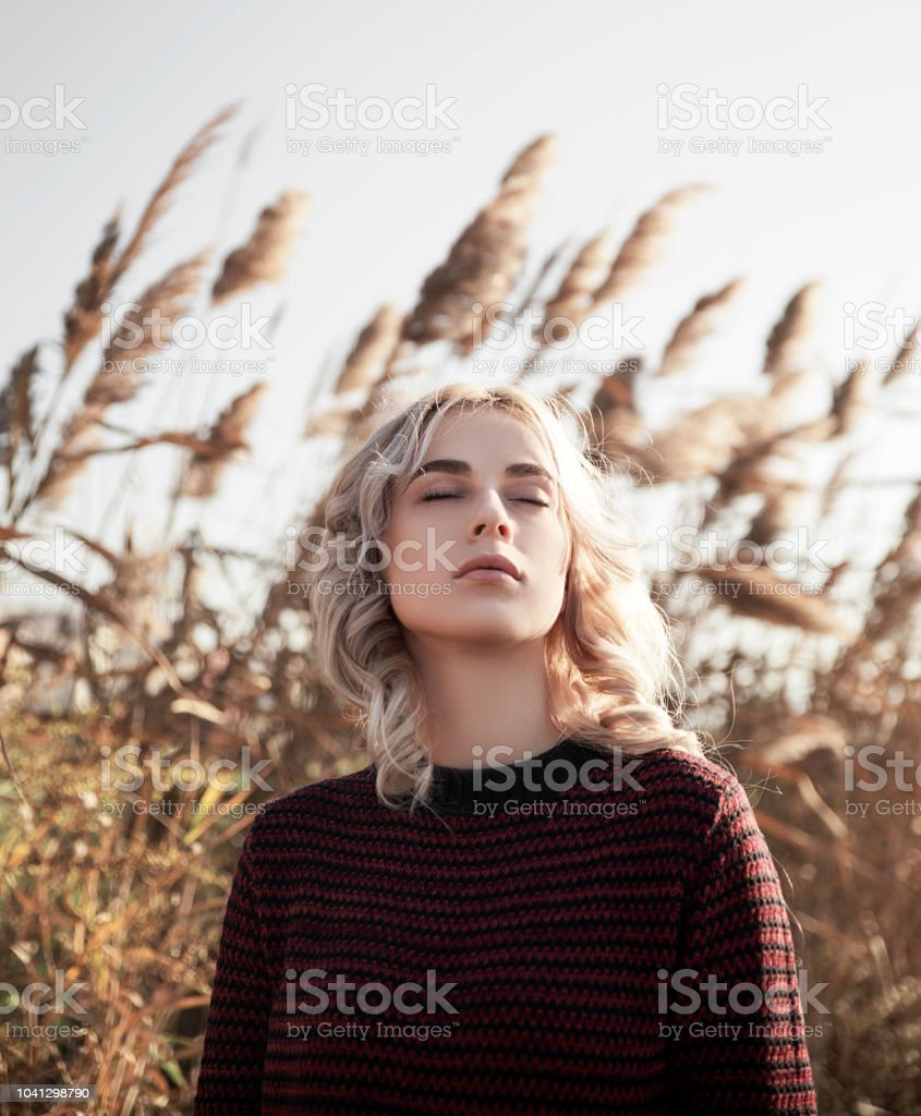 Young blonde woman day dreaming in nature