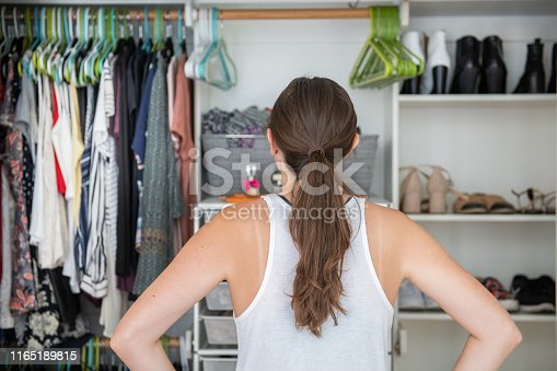 This is a young female adult with her hands on her hips trying to decide what to wear from her well organized closet.