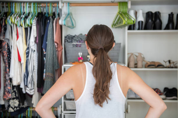 Young Woman Deciding What to Wear From Her Closet This is a young female adult with her hands on her hips trying to decide what to wear from her well organized closet. arrange stock pictures, royalty-free photos & images