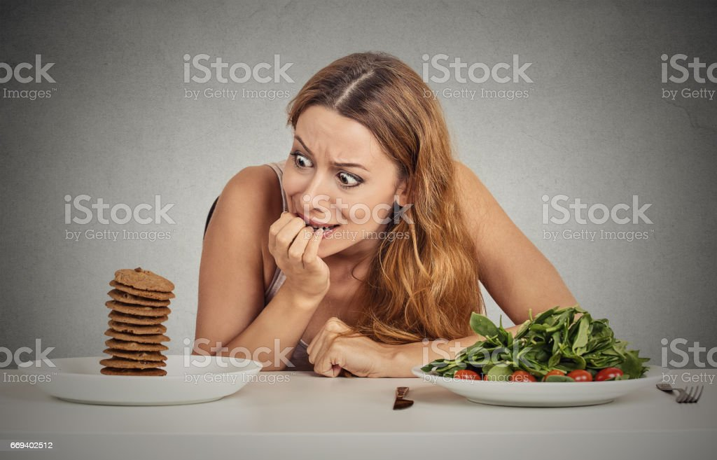 young woman deciding whether to eat healthy food or sweet cookies she is craving sitting at table - foto de acervo