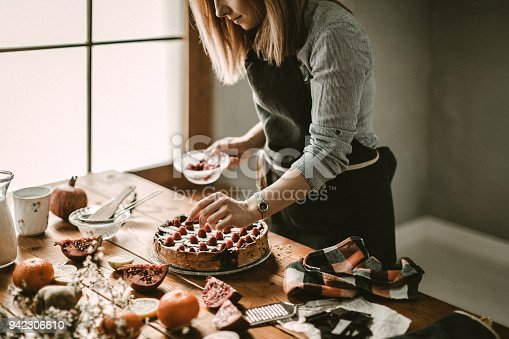 Young woman decorating cake