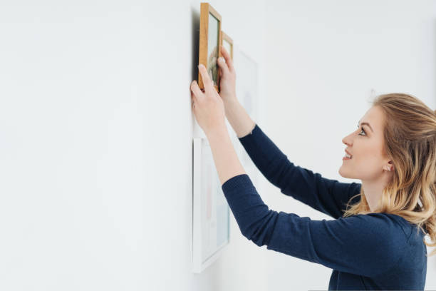 Young woman decorating her home hanging pictures stock photo