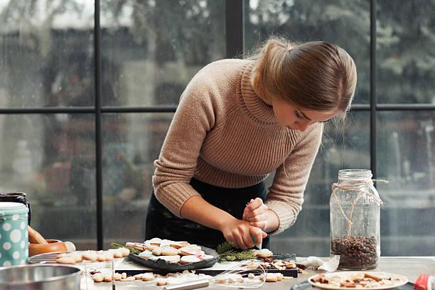 young woman decorating pastry at kitchen - kochkunst stock-fotos und bilder