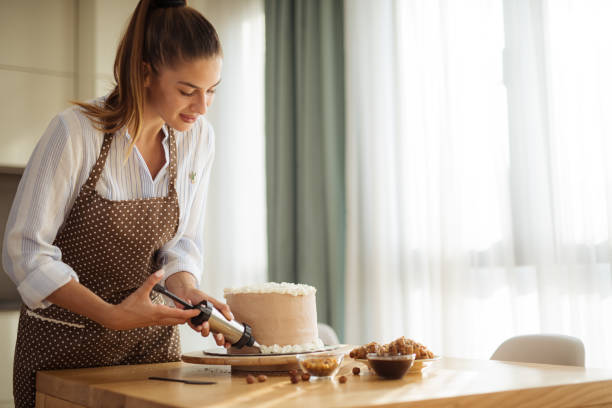 Young woman decorating the cake Young woman decorating the cake decorating a cake stock pictures, royalty-free photos & images