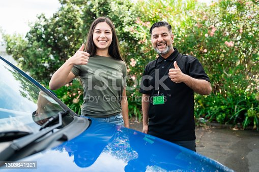 Young girl taking lessons for driving on the road in Auckland, New Zealand.