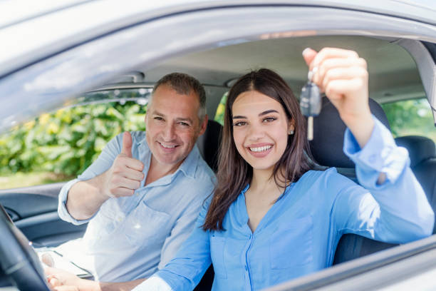 Young woman delighted having just passed her driving test Young woman delighted having just passed her driving test.  Positive face expression driving instructor stock pictures, royalty-free photos & images