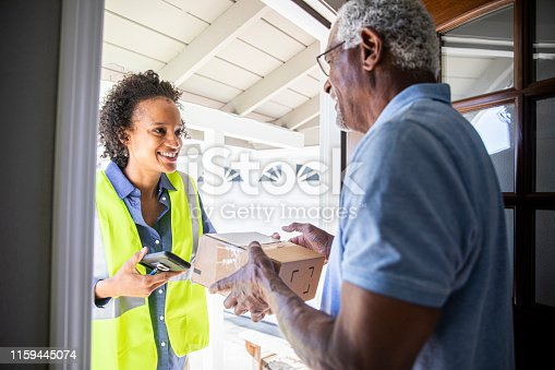 istock Young Woman Delivering Package to Senior Man 1159445074