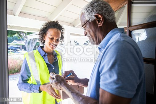 istock Young Woman Delivering Package to Senior Man 1159445128
