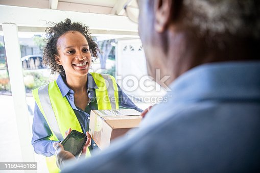 istock Young Woman Delivering Package to Senior Man 1159445168
