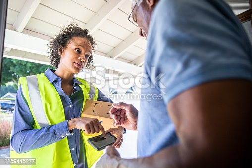 istock Young Woman Delivering Package to Senior Man 1159445277