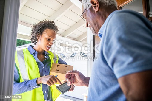 istock Young Woman Delivering Package to Senior Man 1159445975