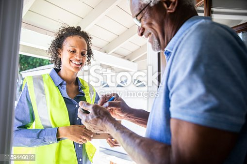 istock Young Woman Delivering Package to Senior Man 1159446012