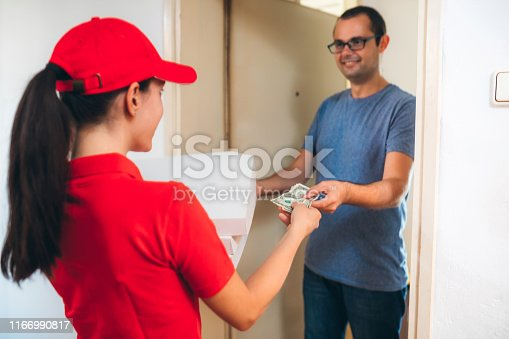 Young caucasian female delivery person giving Pizza  boxes to handsome young man at doorstep