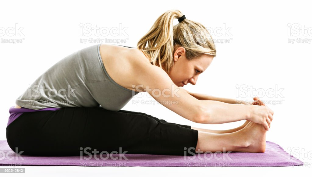 Young woman demonstrating Paschimottanasana or seated forward bend yoga posture - Royalty-free Adult Stock Photo