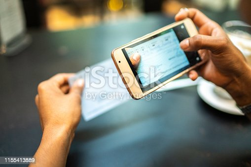 istock Young woman depositing check by phone in the cafe 1155413889