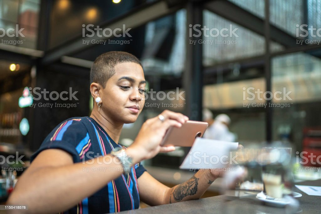 Young woman depositing check by phone in the cafe Young woman depositing check by phone in the cafe 25-29 Years Stock Photo