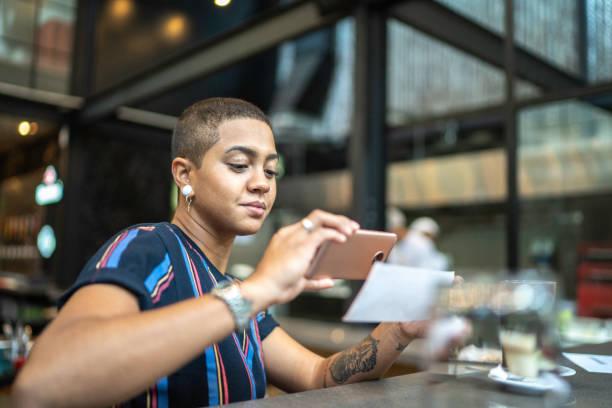giovane donna deposita assegno per telefono al bar - dispositivo informatico portatile foto e immagini stock