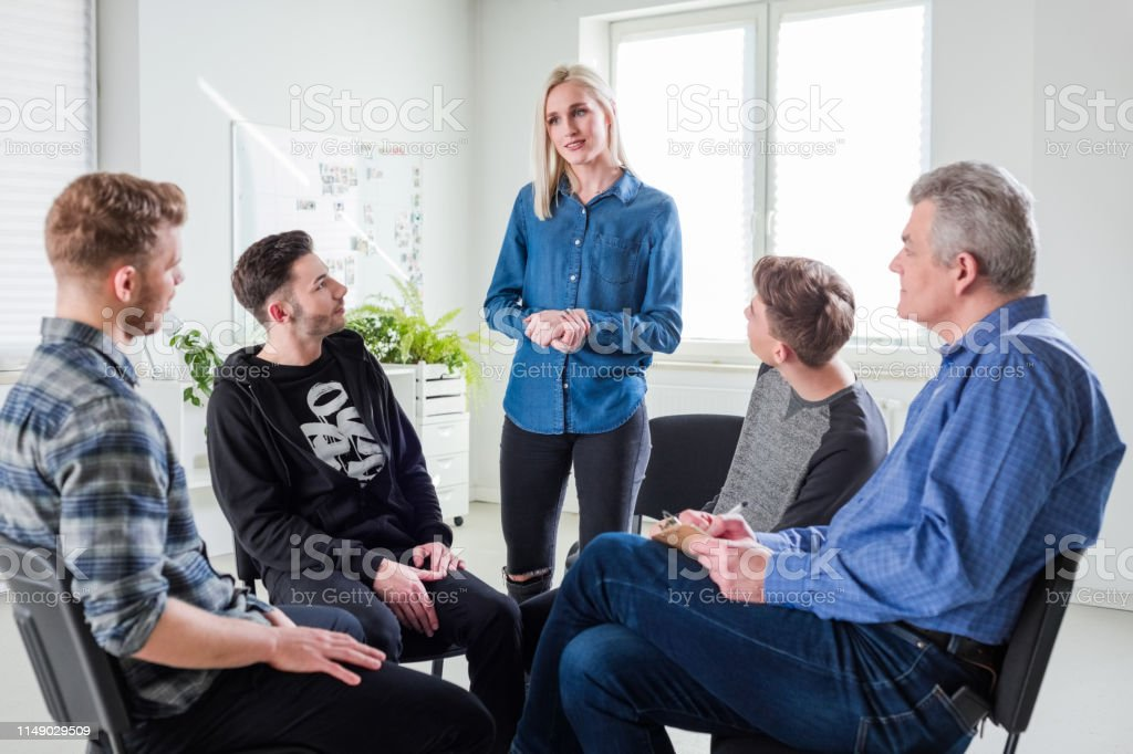 Young woman discussing problems in group therapy Young woman sharing problems with friends and mental health therapist. Mature social worker is with young university students in lecture hall. They are in group therapy at university. 18-19 Years Stock Photo