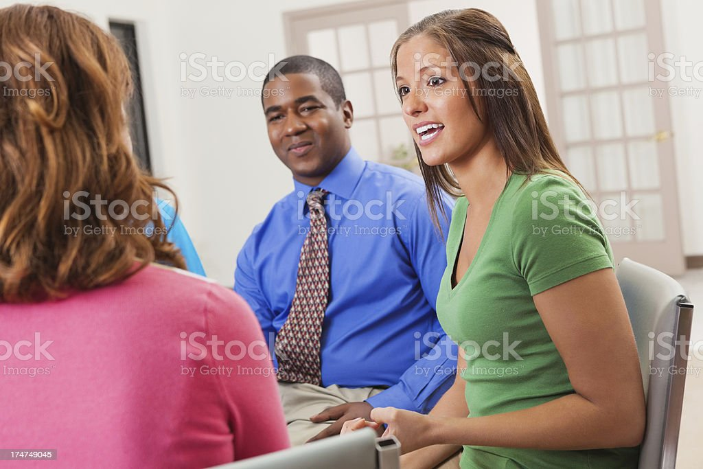 Young woman discussing something with support team or group royalty-free stock photo