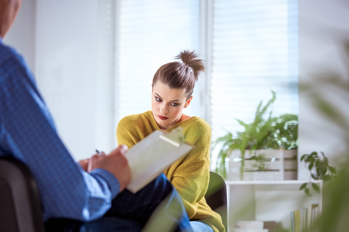 Young Woman Discussing With Therapist Stock Photo - Download Image Now