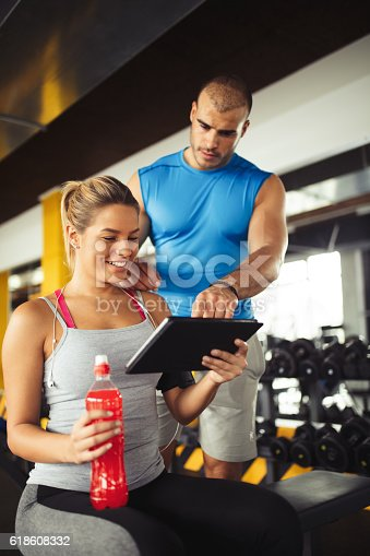 860045834istockphoto Young woman discussing workout plan with fitness instructor 618608332