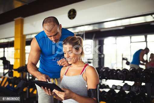 istock Young woman discussing workout plan with fitness instructor 618608502