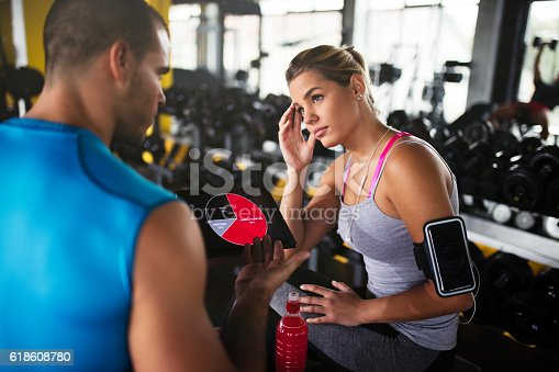 860045834istockphoto Young woman discussing workout progress with fitness instructor 618608780