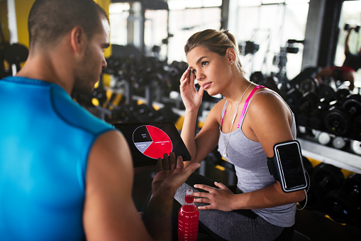 860045834 istock photo Young woman discussing workout progress with fitness instructor 618608780