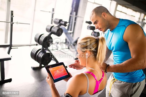 860045834istockphoto Young woman discussing workout progress with fitness instructor 624912322