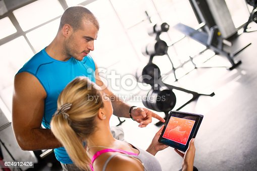 860045834istockphoto Young woman discussing workout progress with fitness instructor 624912426