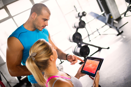 860045834 istock photo Young woman discussing workout progress with fitness instructor 624912426